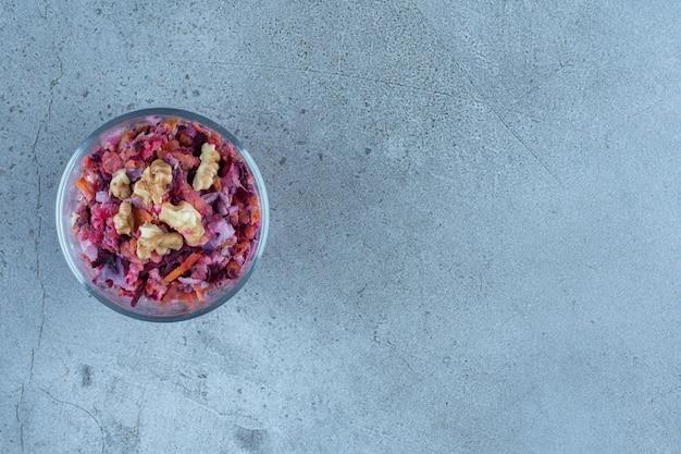 大理石のテーブルの上に小さなビートとクルミのサラダの小さなサービングボウル。