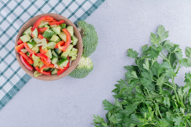Piccola porzione di insalata di peperoni e cetrioli accanto a un piccolo fascio di foglie di prezzemolo su fondo marmo. foto di alta qualità