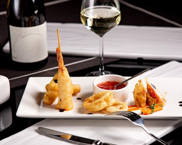 Small serving of seafood starter with crispy fried prawns calamari and sweet chili sauce