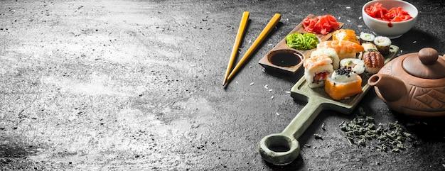 Небольшой набор суши-роллов с зеленым чаем, имбирем и соевым соусом. на черном деревенском фоне