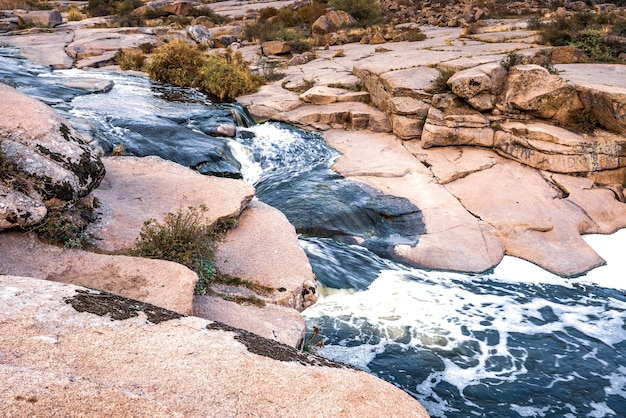 A small shining stream flows among smooth wet and dark stones and dry low trees
