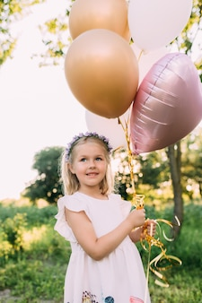 庭にピンクの風船を持つ小さな光沢のある女の子。高品質の写真