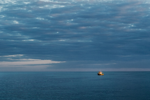 A small ship at sea against the sunset sky.