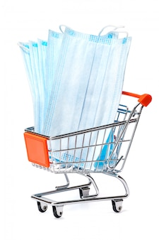 Small shopping cart full medical mask on a white table with clipping path