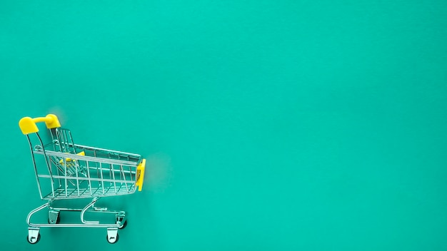 Small shopping cart on green with copy space