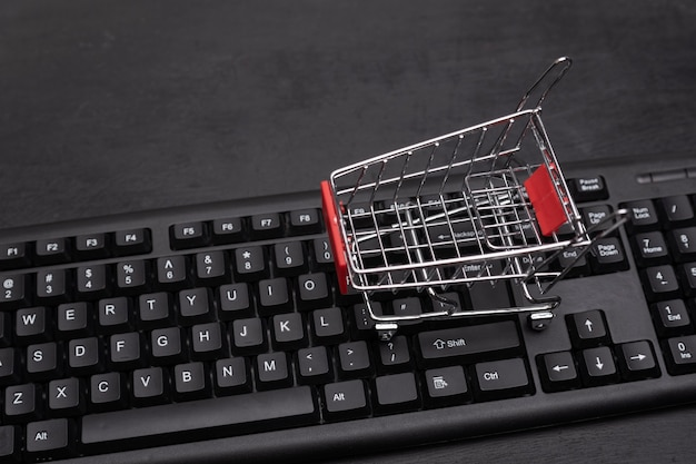 Small shopping cart on the keyboard. online shopping concept. supermarket trolley.