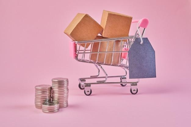 ピンクの壁に空白の値札とコインが付いた小さなショッピングカート。小包でいっぱいのトロリーを買う。