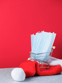 Маленькая тележка для покупок с хирургическими масками, шляпа санты, изолированная на красном фоне, с копией пространства, концепция рождественских покупок, вертикальное изображение