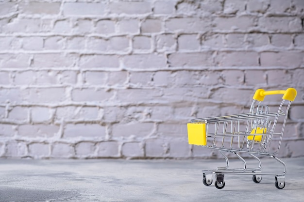 Small shopping trolley on grey background. text space