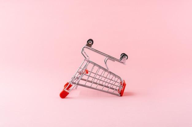 淡いピンクの背景に小さなショッピングトロリー