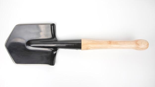 Маленькая лопата для туризма и земляных работ на белом пространстве