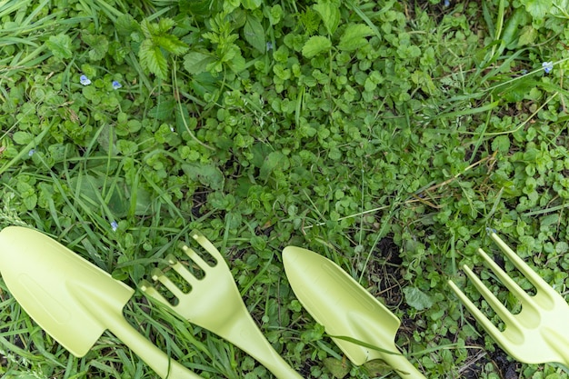 A small shovel and a rake are lying in a row on the green grass in the garden. devices for cultivating the earth, for the purpose of planting plants. tools, decorative tools. cultivation of the land.