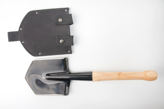 Small shovel for tourism and earthworks with a wooden handle in a plastic case on a white Premium Photo