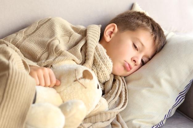 침대에서 작은 아픈 소년 프리미엄 사진