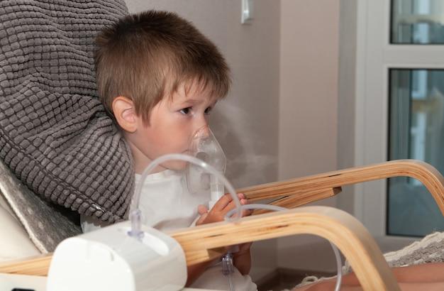 흡입기를 만드는 분무기 마스크를 가진 작은 아픈 소년