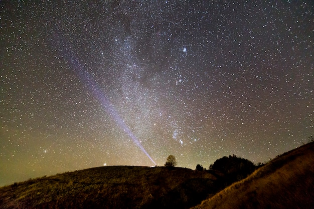 暗い青い夏の星空の下で緑の草が茂った丘の上に懐中電灯を持つ男の小さなシルエット。