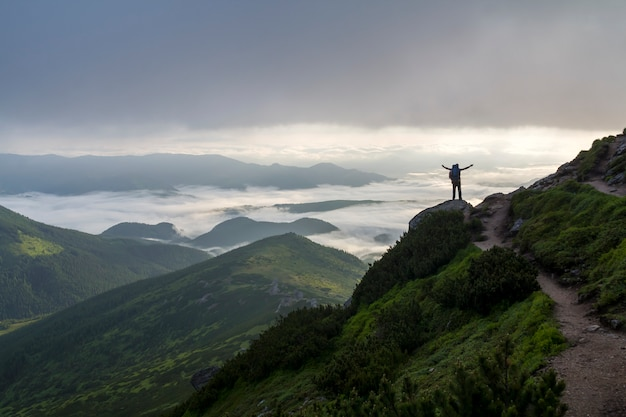 Small silhouette of tourist on mountain with raised hands