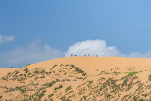 大きな砂丘の上の観光客の小さなシルエット。ダゲスタン。サリクム砂丘。