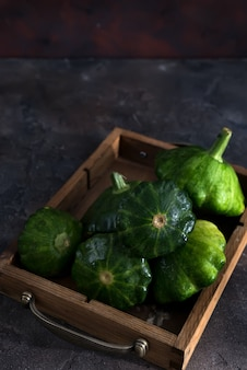 Small size patty pan patisson squash in wooden box on dark wooden background