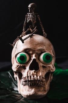 Small skeleton sitting on skull lying on leaf