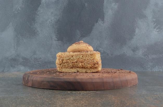 Piccola fetta di torta sormontata da un biscotto su una tavola