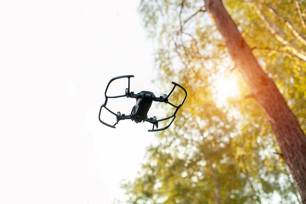 Small smart drone quadrocopter flying on white sky and green trees.