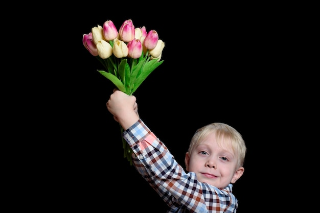 Small smiling blond boy holding a bouquet of tulips. mothers day concept. portrait. isolate on black wall.