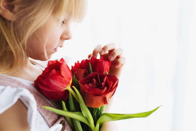Small smiling girl holding bouquet of red tulip flowers. mother's day.