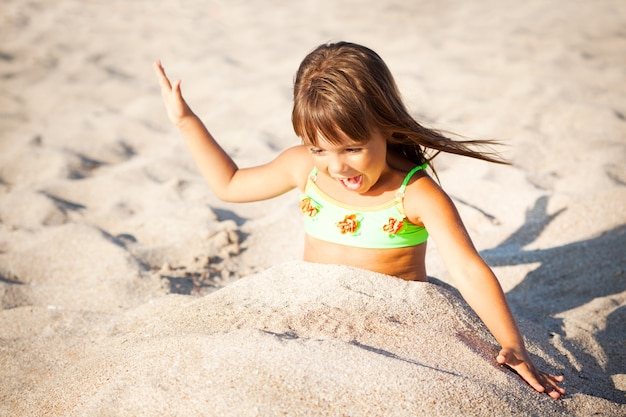 Маленькая улыбающаяся девочка в ярких купальных костюмах сидит и играет с песком на пляже