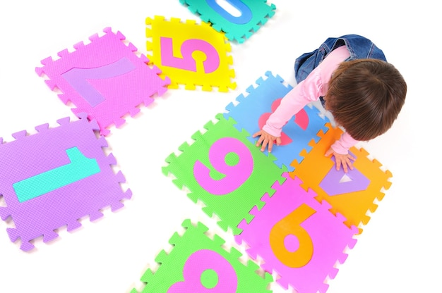 Маленькая улыбающаяся девочка в розовой одежде сидит, изучает числа и держит номер в руках над белой стеной. концепция образа жизни красивых счастливых детей