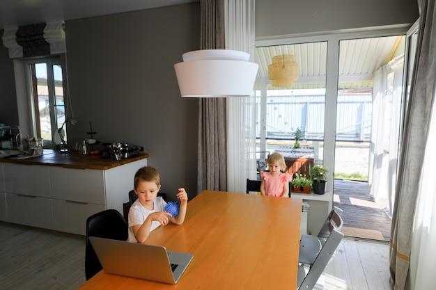 Маленькие улыбающиеся дети брат и сестра смеются и играют в ноутбук, общаются в видеоконференции в чате. просторный уютный домашний интерьер.