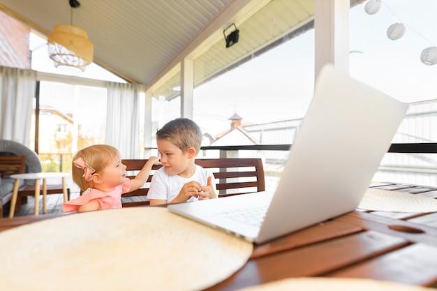 小さな笑顔の子供たちの兄と妹は笑ってラップトップを再生し、ビデオ会議のチャットを伝えます。広々とした居心地の良い家のインテリア。