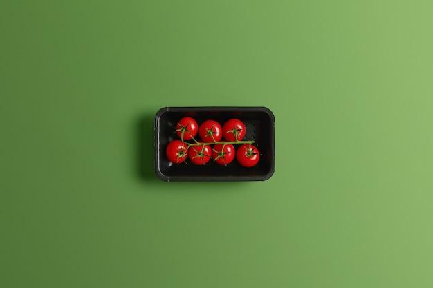 緑の背景に分離された小売包装の小さな滑らかな皮の赤いチェリートマト。健康に欠かせない食物繊維とビタミンcが豊富な甘酸っぱい夏野菜