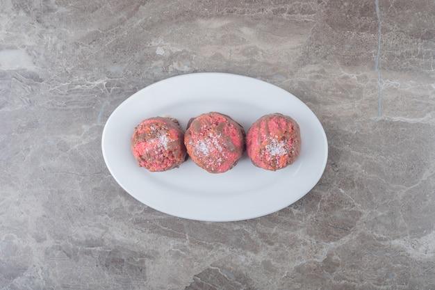 大理石の表面の大皿に小さなスナックケーキ