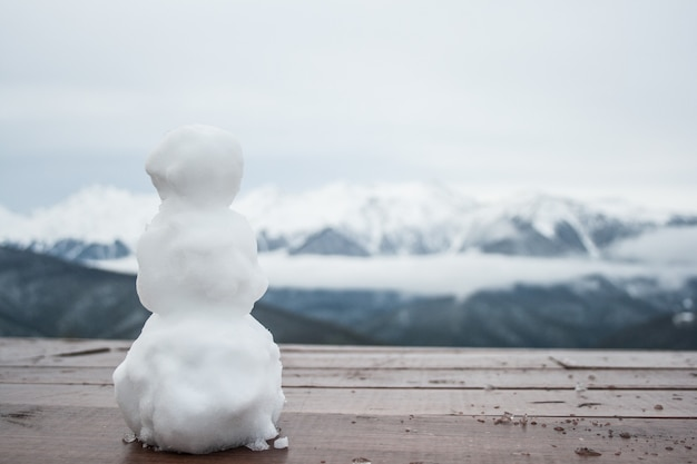 A small snowman is standing on a table, in the background are visible the peaks of mountai