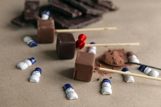 갈색 배경에 향기로운 코코아 가루와 초콜릿이 있는 막대기에 초콜릿 큐브 근처의 작은 눈사람이 닫힙니다. 음식에 크리스마스 장식