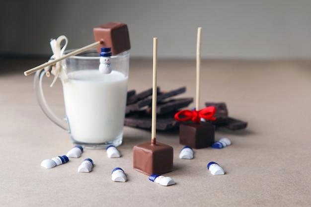 갈색 배경에 우유 컵과 향기로운 코코아, 초콜릿이 있는 막대기에 초콜릿 큐브 근처의 작은 눈사람. 크리스마스 분위기와 장식,