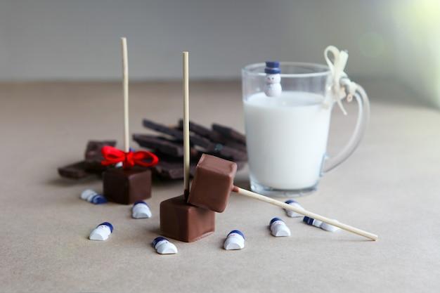 갈색 배경에 우유 컵, 향기로운 코코아, 초콜릿이 있는 막대기에 초콜릿 큐브 근처의 작은 눈사람이 닫힙니다.