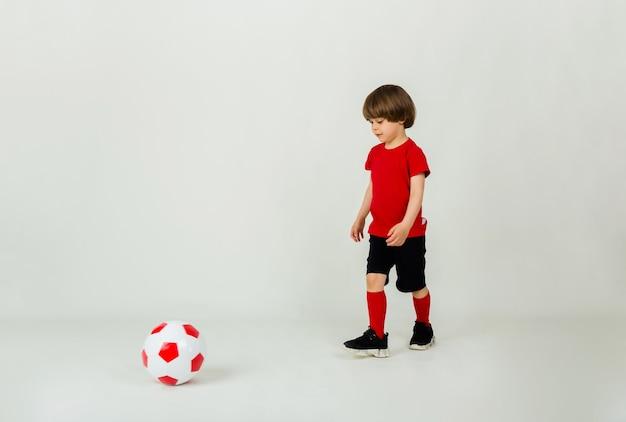 Маленький футболист играет с футбольным мячом на белой поверхности с пространством для текста