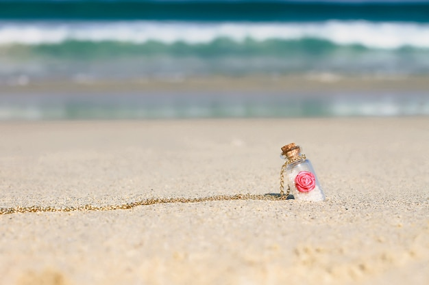 Small souvenir bottle in white sand on the turquoise sea