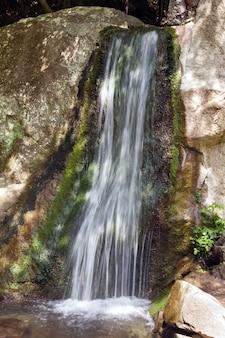 Небольшой весенний горный водопад и скала позади