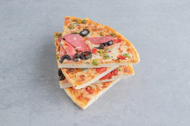 Una piccola pila di fette di pizza su marmo