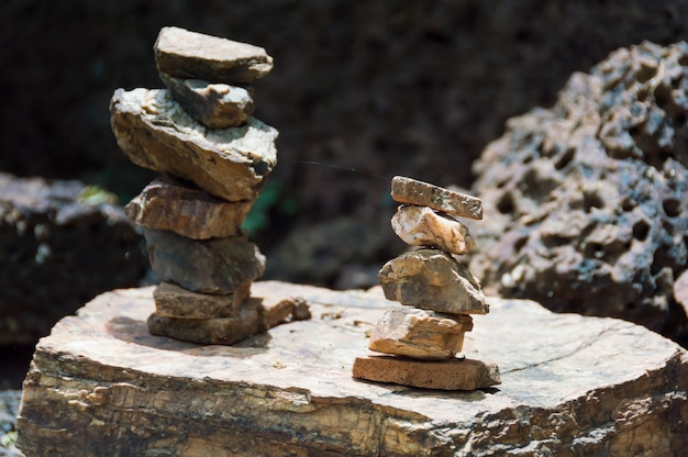 Small stones are stacked in two rows, placed on the surface of large boulder