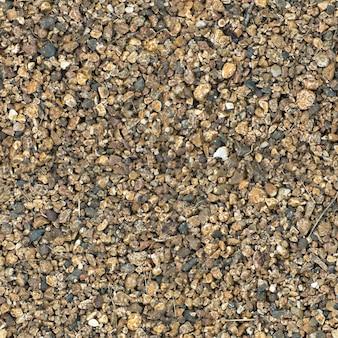 Маленькие камни бесшовной текстуры. бесшовная текстура поверхности покрыта мелкими темно-коричневыми камнями.