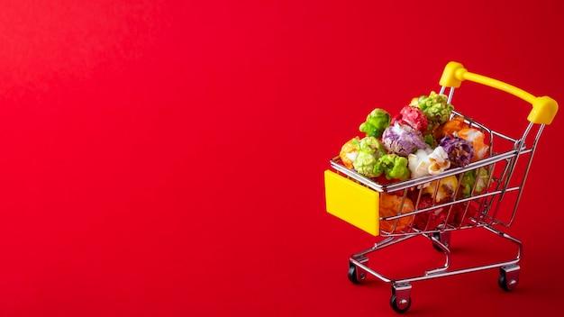 Маленькая тележка для магазина с цветным попкорном, изолированным на красной поверхности