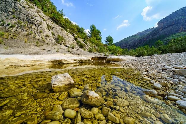 大きな侵食された石のある山の谷の小さな小川。