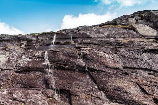 Небольшой поток воды в горах на фоне голубого неба Premium Фотографии