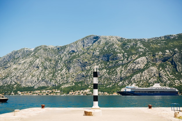 A small striped metal lighthouse on the pier in prcanj montenegro against the backdrop of rocky