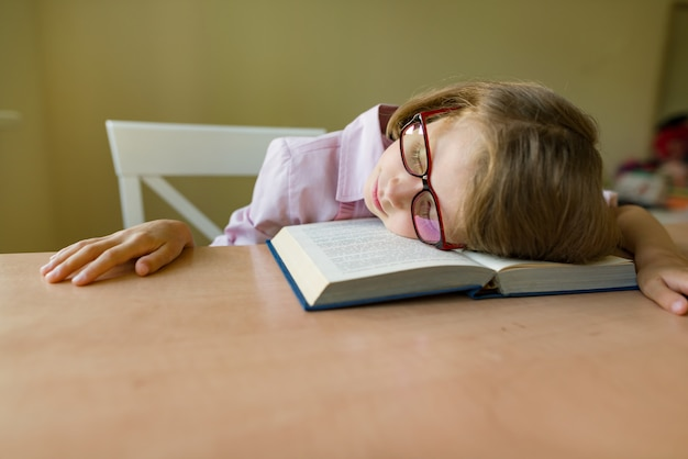 Small student in glasses sleeps at a desk