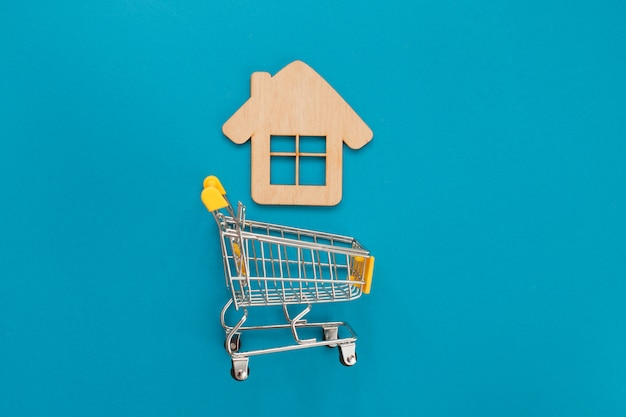 Small supermarket cart for shopping toy wooden house on blue